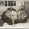 Men eating in the transient camp at Hagerman Lake, Michigan. This is a former lumber camp.