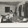 Mother and child in crowded bedroom of home of L.H. Nissen, hired man. He is married, has seven children, one grandchild, all living together in three rooms