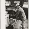 Junkyard owner working on automobile of farmer near Abbeville, Louisiana.