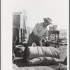 Cowboy tying up bedroll. Cattle ranch near Marfa, Texas.
