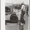 Day laborer cranking tractor on farm near Ralls, Texas.