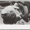 Day laborer putting in cotter pin in front of tractor, farm near Ralls, Texas.