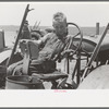 Son of day laborer sitting in tractor seat, large farm near Ralls, Texas.