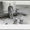 Day laborer filling five gallon cans with gasoline for use in tractors, large farm near Ralls, Texas.