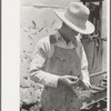 Day laborer looking through box of nuts and bolts, farm near Ralls, Texas.