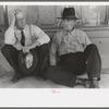 Farmers sitting against wall and squatting on sidewalk, Spur, Texas.