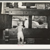 Child playing in front of bureau stuffed with blankets and clothing. Tin Town, Caruthersville, Missouri