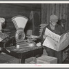 Farmer reading newspaper in feed and general produce store. Eufaula, Oklahoma