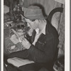 Farm boy rolling a cigarette. Play party in McIntosh County, Oklahoma. See general caption number 26