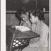 Two Negro children sitting at desk in school. Child in foreground is daughter of Pomp Hall, Negro tenant farmer. Creek County, Oklahoma
