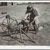 Pomp Hall, Negro tenant farmer, adjusting his cultivator so it will be in readiness for the spring planting. Creek County, Oklahoma