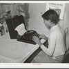 Wife of Pomp Hall, Negro tenant farmer, writing on typewriter. Through union activities this family has developed a desire for higher education. This typewriter is to them a symbol of that education and as such is the most prized family possession