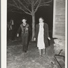 """Couple coming around the corner of the house while playing the game, """"Fishing for love,"""" at play party in McIntosh County, Oklahoma. See general caption number 26"""