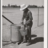 Member of the Arizona part-time farms, Chandler Unit, fixing feed for chickens. Maricopa County, Arizona