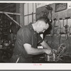 Member of the service department of the United Producers and Consumers Cooperative winding an armature. He was sent by the cooperative to Chicago to learn his trade