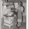 Spanish-American woman stirring pan of cooking beans. Small boy is roasting sweet corn on top of the stove. Chamisal, New Mexico