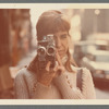 Color photograph of Elaine Summers with film camera