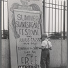 Boy standing next to Summer Shakespeare Festival poster at the East River Park Amphitheatre prior to a New York Shakespeare Festival production of Julius Caesar