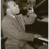 Count Basie seated at piano with Coca-Cola bottle