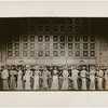 Chorus members standing in front of exterior Automat set in the stage production Face the Music