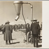 Farmers inspecting new machinery at a farm implement demonstration. Carson County, Texas.