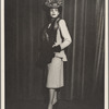 Fashion portrait of a woman in a fox stole, hat, and a suit dress with a waterfall hem on the jacket