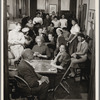 Women playing cards at various tables a the parlour
