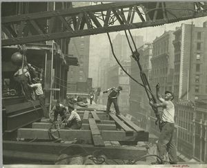 Workers guiding hoisting cable