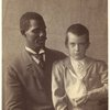 African American man holding a Caucasian boy in sailor suit, ca. 1890s