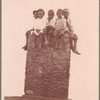 Children sitting on a stone structure, 1902.