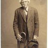 Man in suit, with hat and cane, ca. 1912.