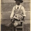 Boy seated on wooden stool.
