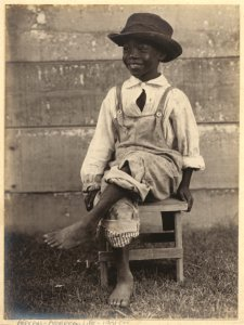 [Boy seated on wooden stool.]