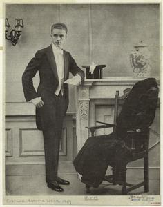 [Man in tuxedo near a fireplace and chair, United States, ca. 1919.]