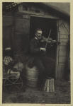 Violin player posed on barrel at the entrance to a shack
