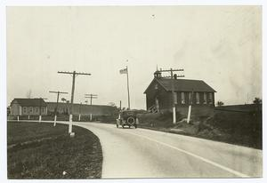 [Paved road, car, and church.]