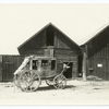 Stagecoach in front of wooden buildings]