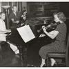1952 Music Period, woman in polka dot dress playing violin next to two men at piano