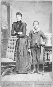 Unidentified standing figures: woman, her folded arms leaning on back of chair, and young man, probably her son, left hand on book.]