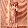 Studio photo of Loie Fuller in a costume with flower garlands.