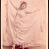 Studio photo of Loie Fuller holding her skirt out.