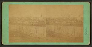 [Elgin: general view showing churches, river, homes, a home with trees in the yard in bloom, a street view showing covered wagon.]