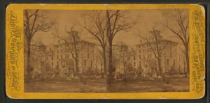 [View of people in yard of building that may be a home.]
