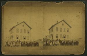 [View of unidentified students and teachers in front of wood frame school.]