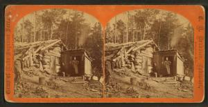 [Woman stands in doorway of log cabin] on the Northern Pacific Road.