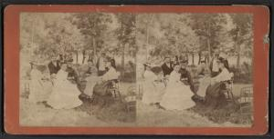 [Portrait of a group of men and women (one with a child on her lap) sitting in chairs on a lawn.]