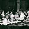 Stephen Sondheim on piano and Leonard Bernstein standing amongst female singers rehearsing for West Side Story (variant).