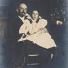Photograph of Potter with his daughter on lap.