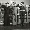 Three Military Men Salute in Front of Bookshelf in U.S.O. Library