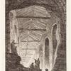 [Figures looking inside the large opening in an exterior wall revealing the light-filled interior of a structure with a series of arched entryways.]